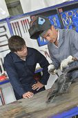 Trainee with instructor using welding machine poster