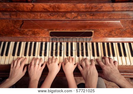 Family of three people is playing the piano