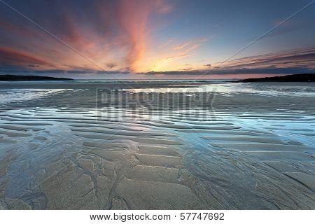 Rising Tide On Sandy Beach At Sunset