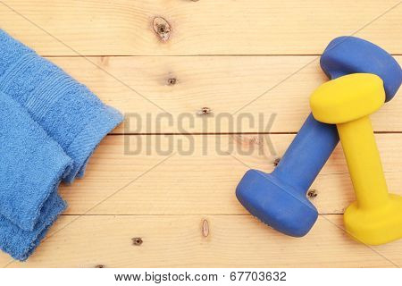 Towel and dumbbells on the wood