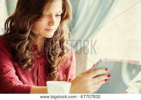 Young smiling woman is drinking coffee in a cafe