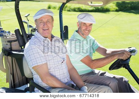 Golfing friends driving in their golf buggy smiling at camera on a sunny day at the golf course