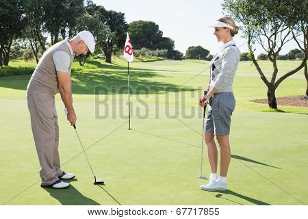 Golfing couple on the putting green at the eighteenth hole on a sunny day at the golf course