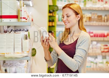 Young woman holding cosmetics in her hand in drugstore department of a supermarket