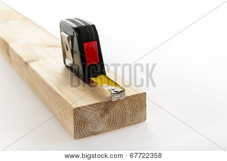 Metal imperial metric tape measure measuring two by four lumber on white background