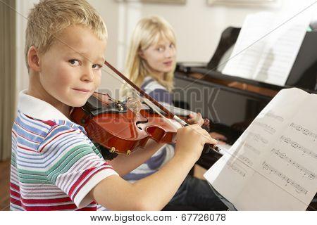 Boy and girl playing violin and piano at home