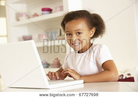 Young girl working on laptop at home