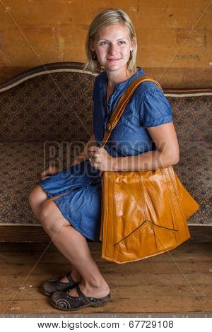 Blonde Woman With Light Brown Purse On Antique Couch