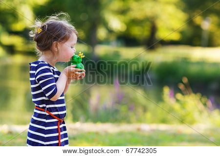 Adorable Little Girl Giving A Kiss To Rubber Frog