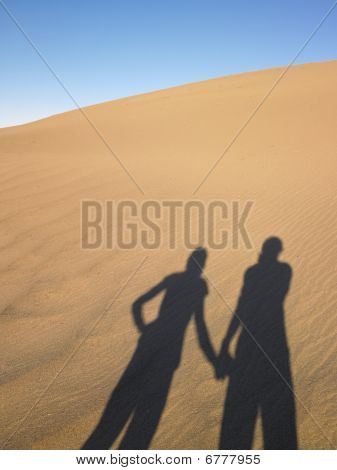 Shadow Of Two People On Sand Dune