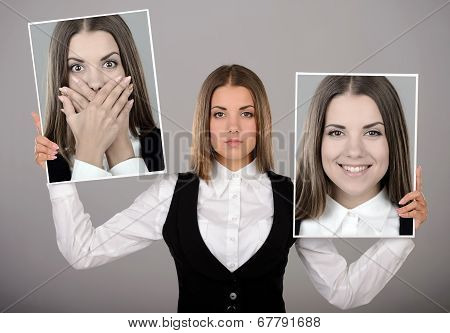 A young business woman holds two portraits of different emotions to choose from today. Gray background poster