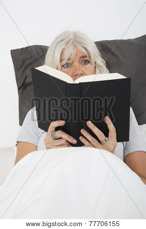 Close up of a Mid age woman reading book in bed, from high angle view