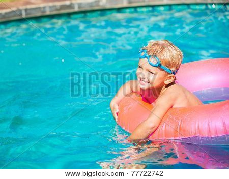 Young Kid Having Fun in the Swimming Pool On Inner Tube Raft. Summer Vacation Fun.