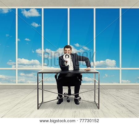 angry businessman screaming with megaphone and looking at camera in the light office with big windows