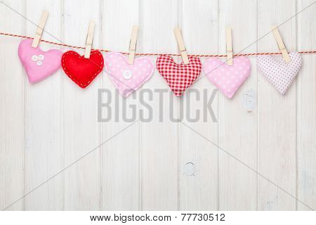 Valentines day toy hearts hanging on rope over white wooden background with copy space