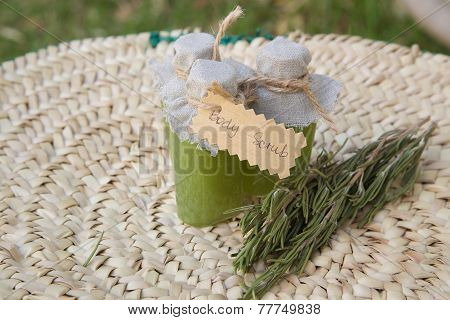 Rosemary body scrub and several rosemary branchlets in the background