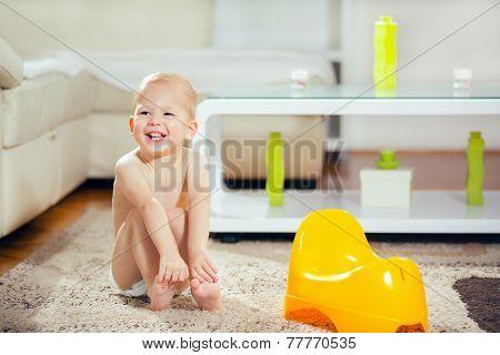 Little baby boy sitting next yellow potty