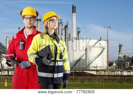 Two safety specialists monitoring the perimeter of a petrochemical refinary, using electroncial devices, such as cb radios and tablets poster