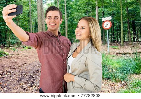 A couple taking a selfie in front of a sign in the woods near a radio telescope, forbidding the use of cell phones, mobile phones and other transmitting equipment. poster