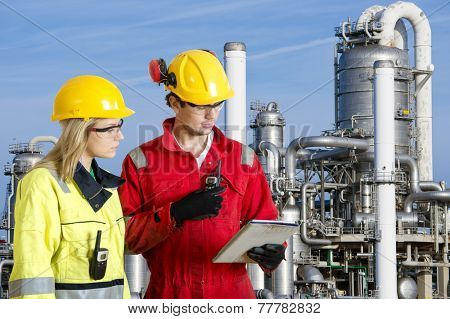 Two engineers going through routine checks, working at a petrochemical oil refinery using cb radios and a tablet computer