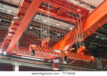 Large-tonnage industrial orange Goliath crane loading of goods in factory mill poster