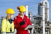 Two engineers going through routine checks, working at a petrochemical oil refinery using cb radios and a tablet computer poster