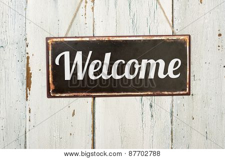 Old Metal Sign In Front Of A White Wooden Wall - Welcome