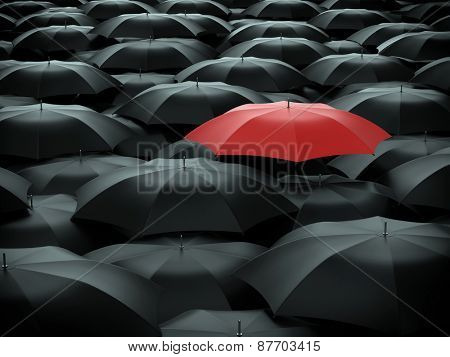 Red umbrella over many black umbrellas