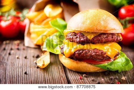 Hamburger with fries on wooden table. Cheeseburger on fresh buns with succulent beef patties and fresh salad ingredients served with French Fries on a wooden table poster