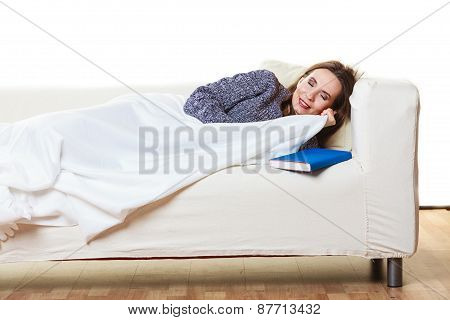 Health balance sleep deprivation concept. Sleeping woman on sofa. Girl lying on couch with book relaxed or taking power nap after lunch. poster