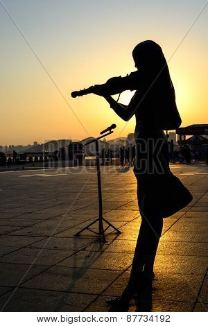 Silhouette Of Girl Playing The Violin