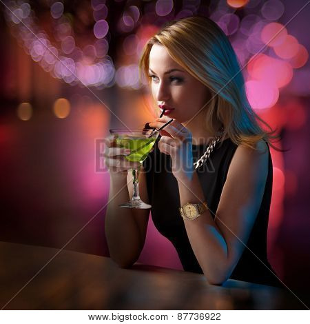 Woman Sipping Her Cocktail While Looking Around