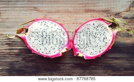 Juicy pink pitaya cut in two pieces on wooden table closeup poster