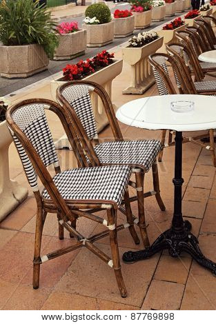 French Sidewalk Cafe With Small Round Tables And Wicker Chairs