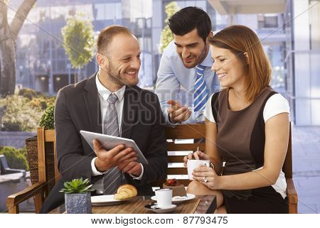 Happy caucasian business team having an outdoor meeting at restaurant using tablet computer.