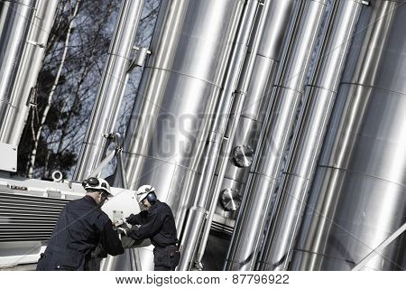 oil, fuel and gas workers with giant gas-pipes machinery