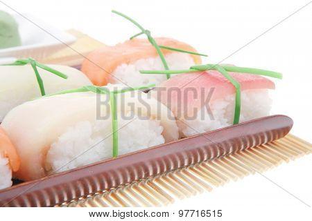 Japanese Cuisine - Set of Tuna (maguro) Salmon (sake) and Eel (unagi) Nigiri Sushi  with Wasabi and Ginger on bamboo mat isolated over white background