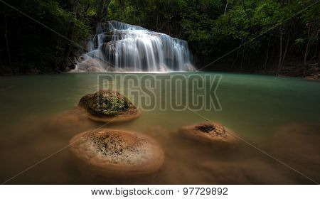 Wet stones in river stream in wild rainforest with scenic waterfall cascades at evening. Beautiful nature background
