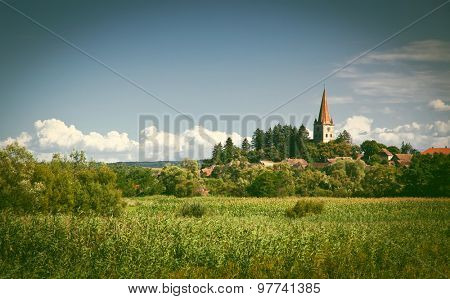 Idyllic rural view of gently rolling patchwork farmland and village
