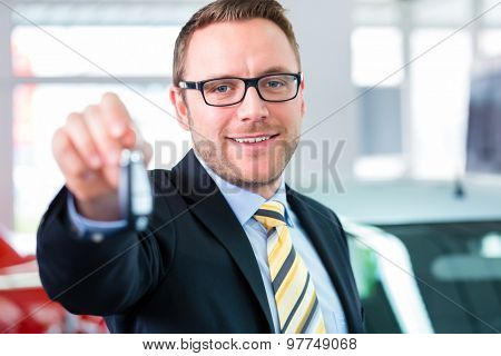 Salesman handing over auto key at car dealership