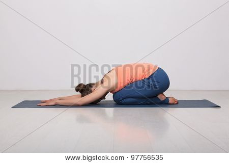 Beautiful sporty fit yogini woman practices yoga asana balasana (child's pose) - resting pose or counter asana for many asanas in studio poster