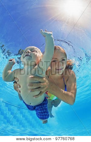 Mother With Child Swimming And Diving Underwater In Pool