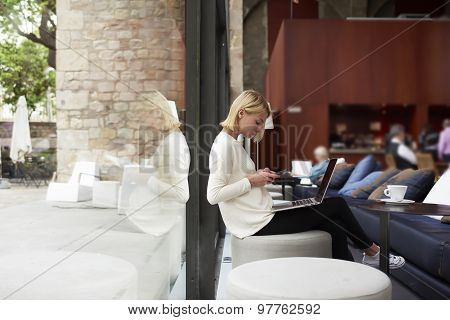 Female freelancer connecting to wireless via smartphone while having a coffee in modern cafe