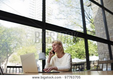 Beautiful young female having smartphone conversation while sitting in modern loft interior