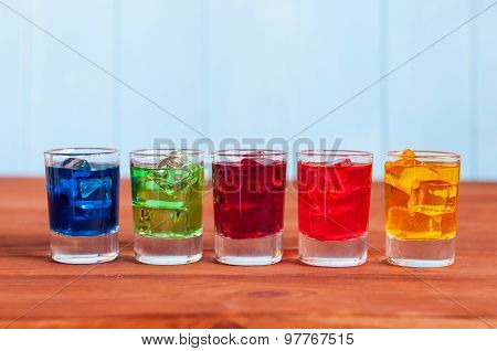 Five cocktails or liqueur on the wooden background