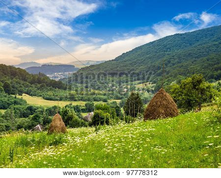 Field With Haystacks On Hillside At Sunrise