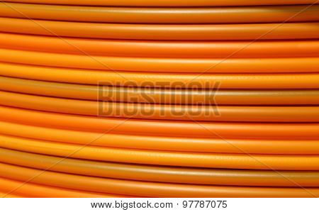 Coils Of Orange Plastic Pipes For The Installation Of Underground Utilities