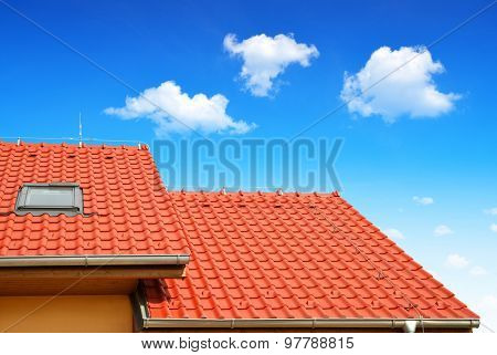 Roof house with tiled roof on blue sky.