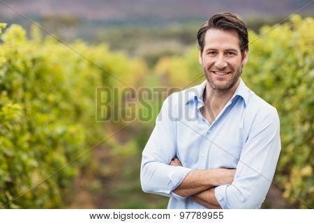 Happy vintner with crossed arms in the fields