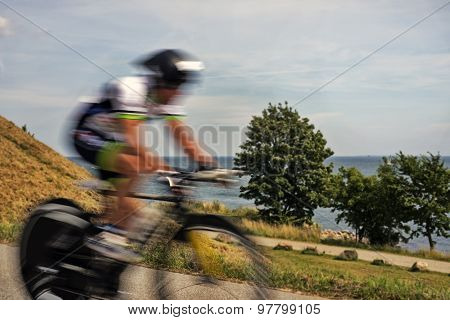 Triathlon bike race cyclists at high speed close to Little Belt in Fredericia Denmark. poster